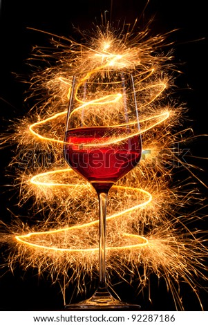 Wine in glass with burning sparklers on black background - stock photo