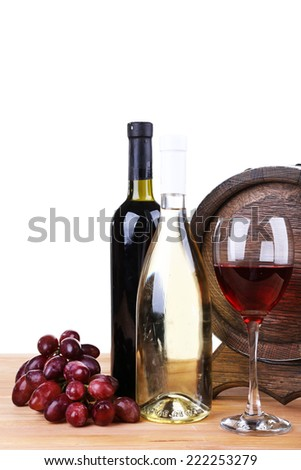 Wine in goblet and in bottles, grapes and barrel on wooden table on white background