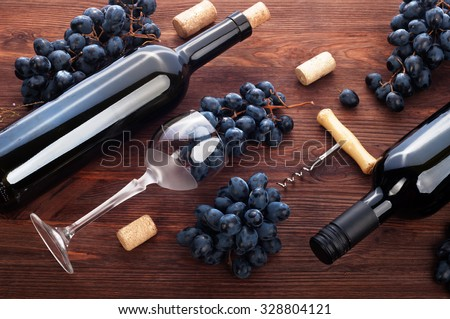 Wine in the bottles and wine in the glass on a dark background; grapes; corkscrew; corks; the substrate for the wine list; drinking wine - stock photo