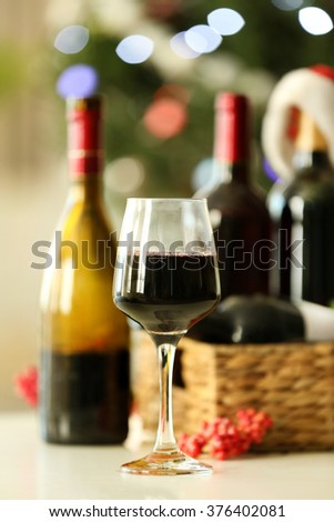 Wine in wicker box and Christmas decor in a room - stock photo