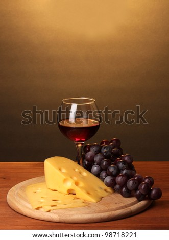 Wine in wineglass and cheese on wooden table on brown background