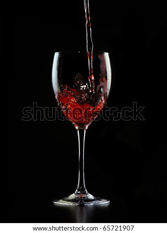 Wine is poured into a glass on a black background - stock photo