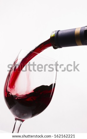 Wine is poured into stemmed glass liquid refreshment red alcohol drink winery isolated white - stock photo