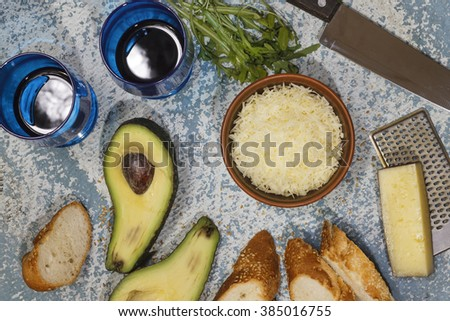 Wine, Italian cuisine. Wine in a blue glass on a wooden table  top view, closeup.  Parmesan cheese, avocado, arugula, croutons, toasts. - stock photo