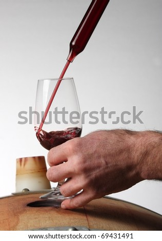 Wine maker taking a sample of red wine from an oak barrel using a glass wine thief, or pippet. - stock photo