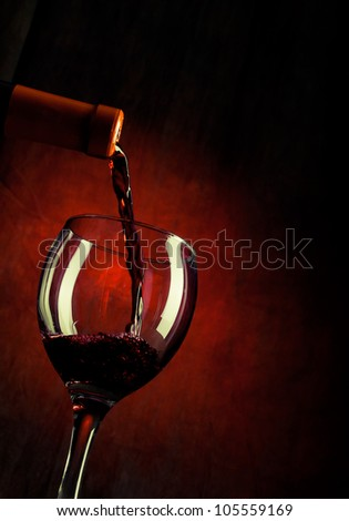 Wine pouring down from a wine bottle - stock photo