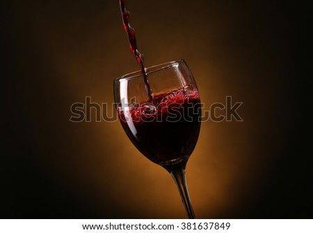 Wine pouring in glass on brown background - stock photo