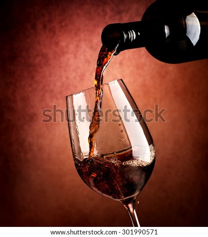Wine pouring in wineglass on a brown background