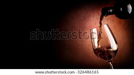Wine pouring in wineglass on the brown background - stock photo