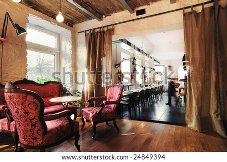 Wine restaurant interior, with vintage chairs and table, with waiter ready to serve - stock photo