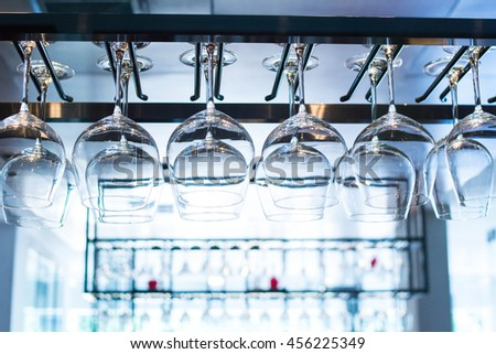 Wine's glass hanging on bar. Empty glasses for wine above a bar rack. A lot of glasses hanging in a row, Selective focus and lighting from background - stock photo