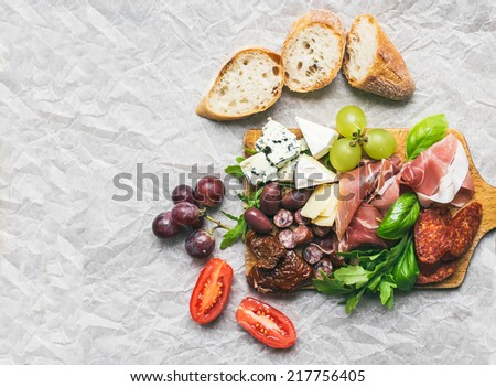 Wine set consisting of smoked meat, sausages, cheese, grapes, cherry-tomatoes, olives, basil leaves, arugula, dried tomatoes and baguette slices on a rustic wood board over a white paper background - stock photo