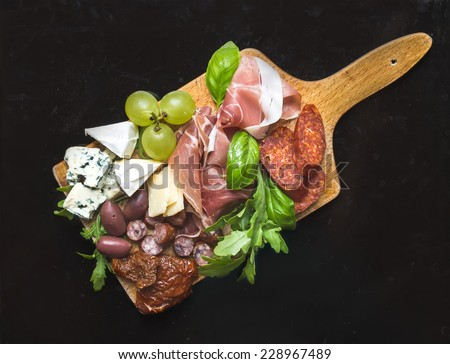 Wine set consisting of smoked meat, sausages, cheese, grapes, cherry-tomatoes, olives, basil leaves, arugula and dried tomatoes on a rustic wood board over a black metal background  - stock photo