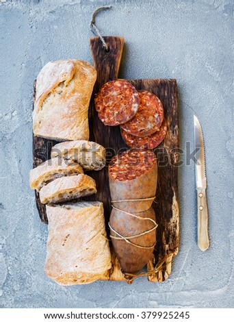 Wine snack set. Hungarian mangalica pork salami sausage and rustic bread on dark wooden board over a rough grey-blue concrete background, top view, vertical - stock photo