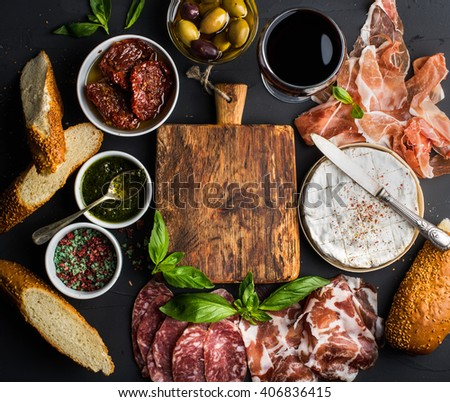Wine snack set with empty wooden board in center. Glass of red, meat selection, mediterranean olives, sun-dried tomatoes, baguette slices, camembert cheese and spices on black background, top view - stock photo