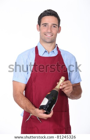 wine steward holding a bottle of champagne - stock photo
