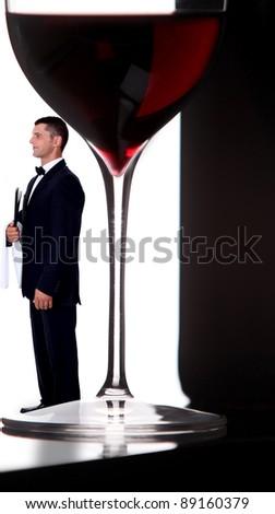 wine steward posing next to giant glass of wine - stock photo