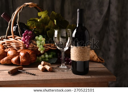 Wine still life on a rustic wood table with warm afternoon window light. An old fashioned cork screw, a basket of grapes and leaves, bread and some corks and an empty wineglass round out the scene.  - stock photo
