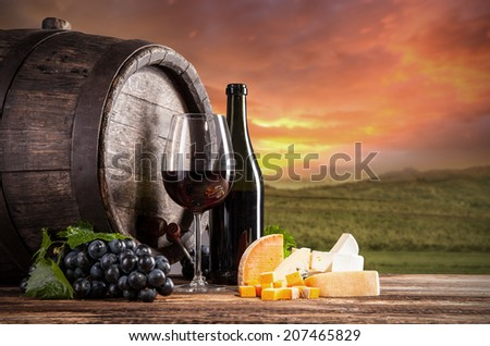 Wine still life on wooden keg with vineyard on background - stock photo