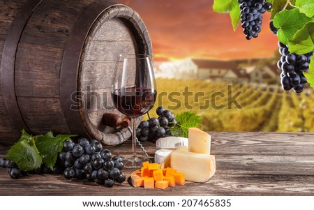 Wine still life on wooden keg with vineyard on background