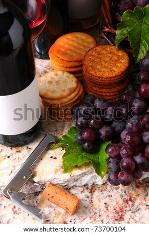 Wine Still life with corkscrew, grapes and crackers. Vertical format with side window light. - stock photo