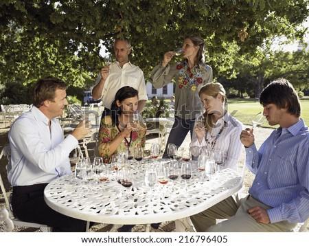 Wine tasters tasting wine. - stock photo