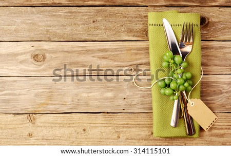 Wine tasting Cutlery with wine grapes decorative wooden table with copyspace - stock photo