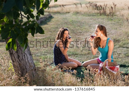 Wine tasting young women during a picnic in golden evening light - stock photo