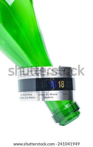 Wine thermometer on the green bottle neck - stock photo