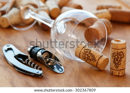 Wine tools and corks on wooden surface - stock photo