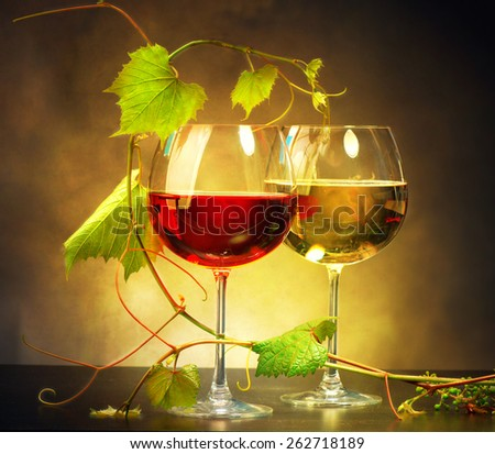 Wine. Two Glasses of wine. Glass of red and white wine decorated with grape leaves. Vine leaf. Sepia toned art design - stock photo