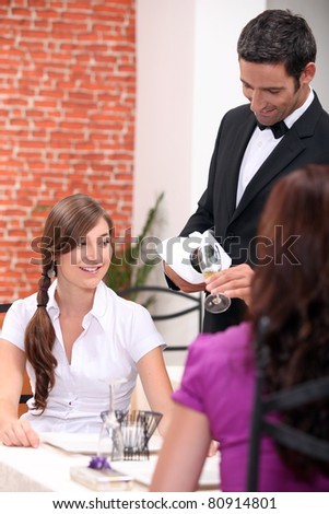 wine waiter pour out wine for customers at a restaurant - stock photo
