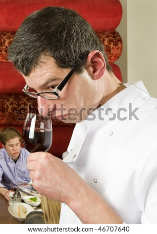 wine waiter savoring wine in a restaurant witch customers on the background - stock photo