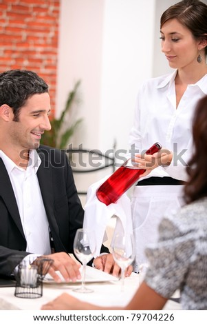 wine waitress showing a wine bottle to a customer - stock photo
