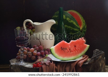 Wine, water-melon, grapes, guelder-rose and white jug - stock photo