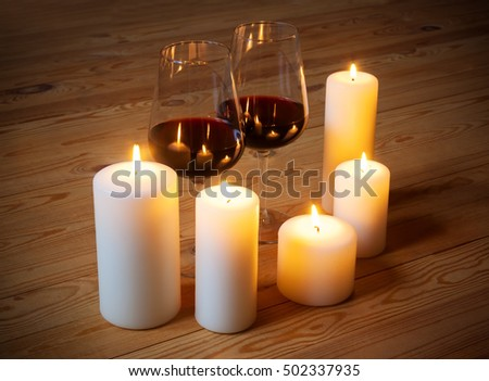 Wine with candles on wooden background