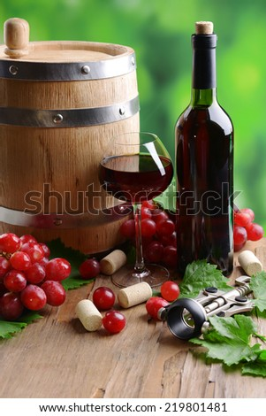 Wine with grapes on table on bright background - stock photo
