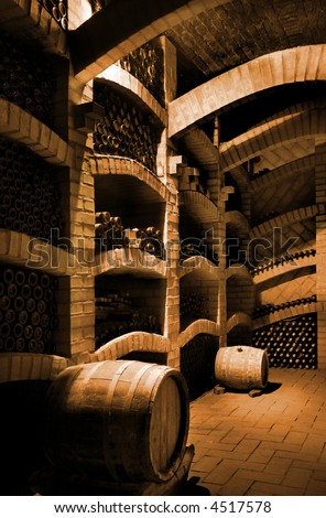 Winebottles stacked in the old cellar of the winery. - stock photo
