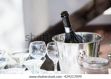 Wineglass and a bottle of chilled champagne are in an ice bucket for guests on wedding reception before wedding ceremony. - stock photo