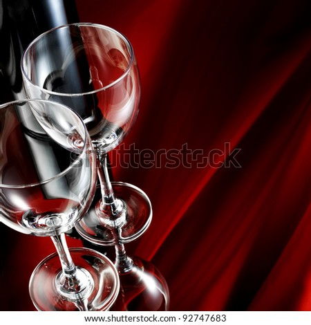 Wineglass and bottle on mirror table - stock photo