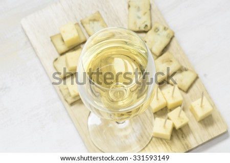 Wineglass of white wine on a wooden board with appetizers