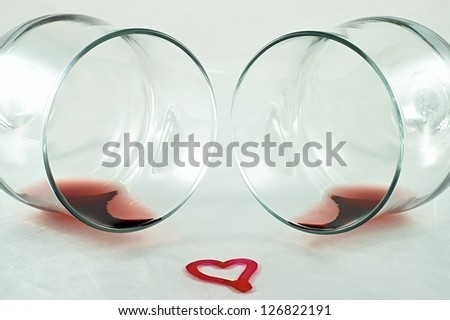 wineglass with a little red wine and heart