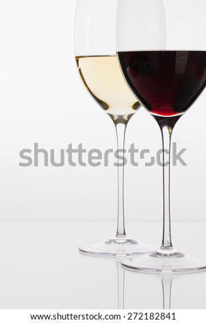 Wineglass with red and white wine on a glass table - stock photo