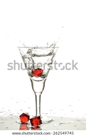 Wineglass with transparent clear water and red crystal a falling into a liquid spattering drops in different directions - stock photo