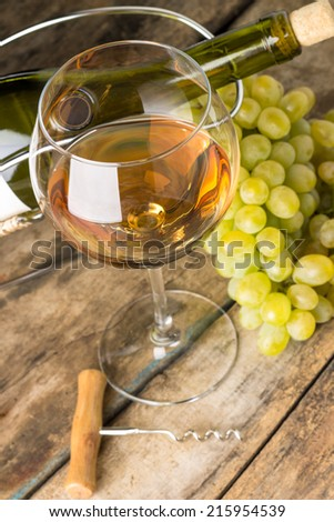 Wineglass with white wine, bottle, corkscrew and cluster of grapes around on wood background - stock photo