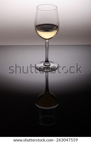 Wineglass with white wine standing on reflective background - stock photo