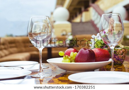 wineglasses and fruits laid on a table, close up outdoor shot - stock photo