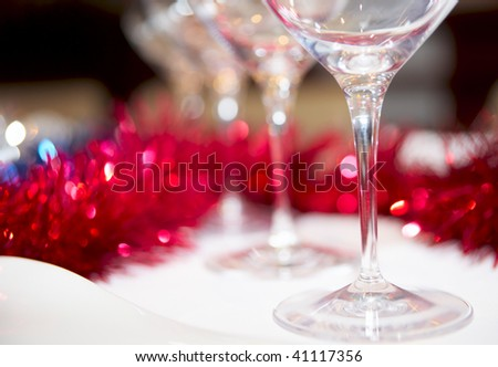 Wineglasses and red decorations in background, shallow focus - stock photo
