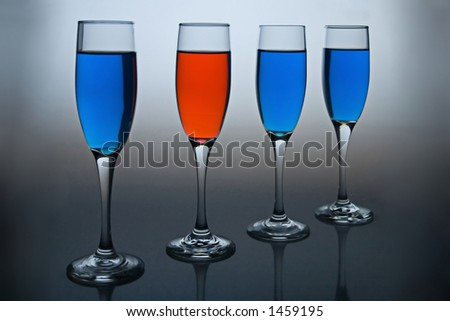 Wineglasses filled with colored liquid - illustrating concepts such as Workplace Diversity, Dare to be Different, or Democrat vs Republican. - stock photo