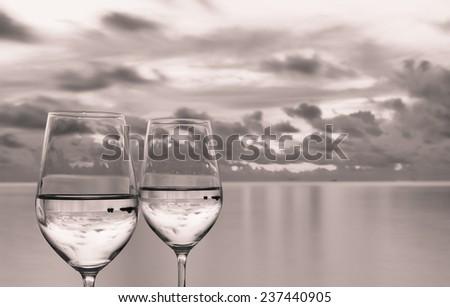 Wineglasses next to a beautiful sunset - stock photo